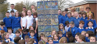 Children at the school with a mosaic they made